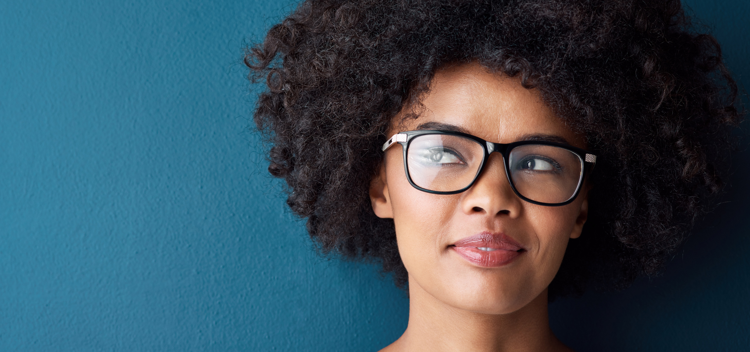 Thinking of ways to use her tax refund on eye care is this young woman wearing glasses looking thoughtful against a blue background.
