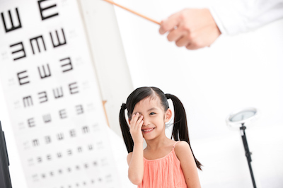 Young girl looking at eye chart.
