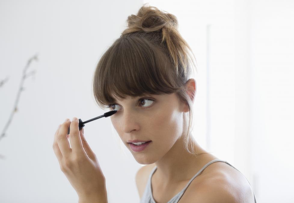 Woman applying mascara next to her eyes