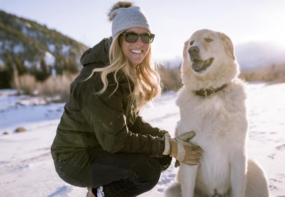 Woman in winter wearing sunglasses with her dog.